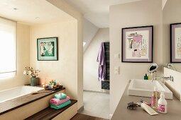 Elegant bathroom in converted attic: sunken bathtub with steps in niche below window opposite washstand