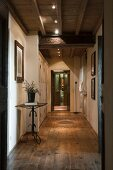 Long hallway with rustic wooden floor and modern spotlights on wood-beamed ceiling