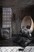 Wicker hanging chair in dark room with wood-burning stove