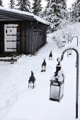 Lanterns in snow leading to black wooden hut