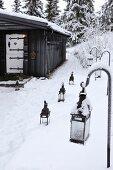 Lanterns in snow leading to black wooden hut