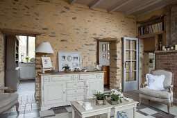 Vintage-style rustic interior; side tables and white sideboard against rough wall