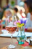 Glass of rosé wine in front of vase of flowers
