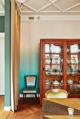 Table in front of display case against turquoise and white ombré-effect wall