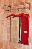Retro metal coat rack in front of mirror on wall with patterned wallpaper
