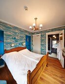Double bed with carved wooden frame in bedroom with patterned wallpaper