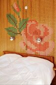 Double bed against perforated panels decorated with cross-stitch cord flower