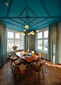 Antique table and chairs below blue-painted ceiling with multiple pendant lamps in meeting room