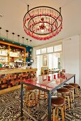 Minimalist counter and bar stools on tiled floor with vintage ornamental pattern in bar; chandelier made from concentric metal rings and cutlery painted pink