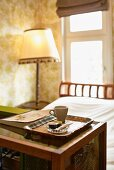 Espresso cup on tray in front of standard lamp next to bed