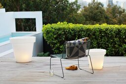 Retro armchair and illuminated planters on wooden terrace