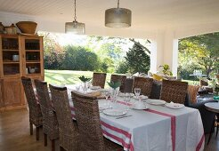 Set dining table, wicker chairs on roofed terrace with view into large garden