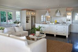 Open-plan interior with white sofa set and free-standing kitchen counter