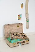 Scatter cushions in open vintage suitcase next to wooden board on wall