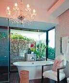 Armchair, stool and chandelier in cosy bathroom