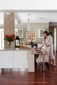Floral armchairs at modern kitchen counter; woman arranging place settings