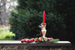 Red apples and pine cones around red candle in silver candlestick