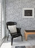 Armchair and designer bedroom bench on marble tiles and against patterned wallpaper