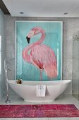 Picture of flamingo on wall above free-standing bathtub in marble bathroom