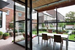 View into modern glass extension with dining area and view of garden