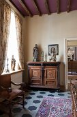 Sculptures and candlesticks on top of antique, elegant cabinet next to window with draped curtains