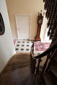 View down winding wooden staircase into hallway with honeycomb floor tiles and antique long-case clock