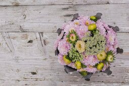 Arrangement of chrysanthemums and yarrow on rustic wooden surface