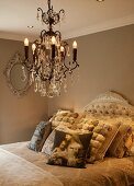 Crystal chandelier above bed with vintage-style scatter cushions and curved headboard in romantic bedroom