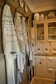 Vintage tea towels and aprons hanging from hooks in front of vintage-style white dresser in corner of kitchen
