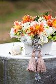 Festliches Blumengesteck mit Silberschmuck und Quasten auf versilbertem Tisch