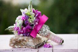 Festlicher Blumenstrauss mit pinkfarbener Schleife und Perlenschmuck, auf Damen Abendtasche mit Pailletten