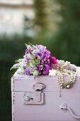 Festlicher Blumenstrauss mit Perlenkette verziert, auf Holztruhe pastellfarben lackiert