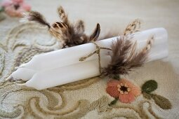 Three white candles tied with cord and decorated with feathers on elegant, embroidered vintage tablecloth