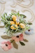 Easter nest made from planted pot with rabbit ornament and wooden eggs on embroidered vintage tablecloth