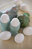 White eggs in turquoise eggcups an bird ornaments