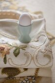 White hen's egg in turquoise eggcup on embroidered tablecloth