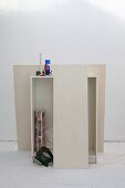 White cabinet, cordless jigsaw, roll of wallpaper, scissors and tools