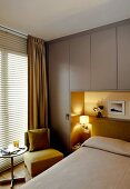 Bed with headboard in illuminated niche of fitted wardrobes, easy chair and bistro table next to window