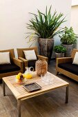 Wicker furniture around coffee table with planters to one side