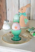 Boiled egg in turquoise eggcup in front of textile rabbit-shaped egg warmers