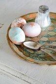 Verschieden gestaltete Ostereier, Silberlöffel und Salzstreuer auf Vintage Tablett