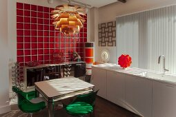 White kitchen counter below vertical louvre blinds, dining table and chairs below classic pendant lamp and retro sideboard against wall covered in red glass tiles