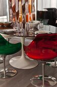Retro shell chairs made from coloured transparent plastic around Tulip Table with place settings