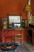 Wooden chair and vintage desk decorated with pictures and wicker ornaments against wall painted rusty red