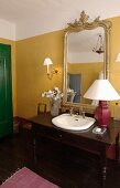 Washstand made from desk with integrated sink and table lamp in front of elegant, gilt-framed mirror on yellow-painted wall