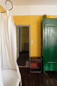 Vintage-style bathtub, shower curtain and green-painted cupboard against yellow wall