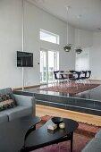 Blick von Loungebereich auf Empore mit Essplatz unter Klassiker-Pendelleuchten