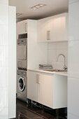 Blick in Waschraum auf Spültisch neben Schrankkorpus mit integrierter Waschmaschine und Trockner