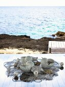 Seashells and net on white wooden table on sea shore