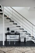 Desk and Ghost chair below staircase in contemporary stairwell